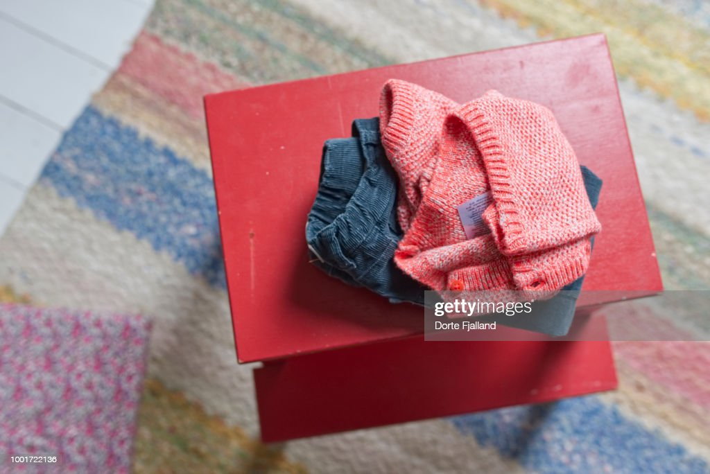 children's clothes, blue corduroy trouser and a red sweater on a red painted stool : Foto de stock