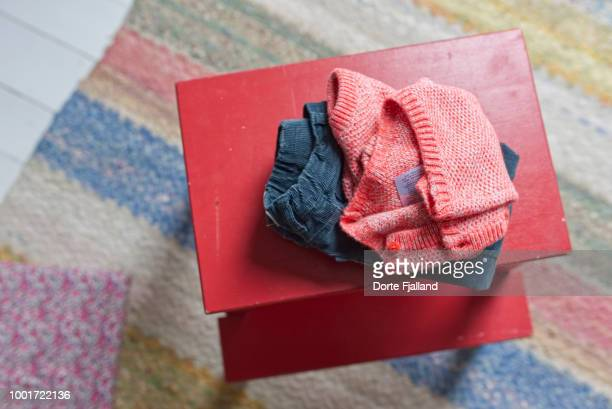 children's clothes, blue corduroy trouser and a red sweater on a red painted stool