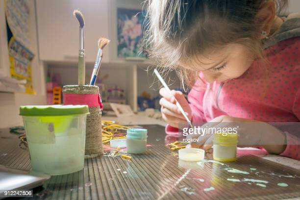 Children's creativity.The child decorates the garland.