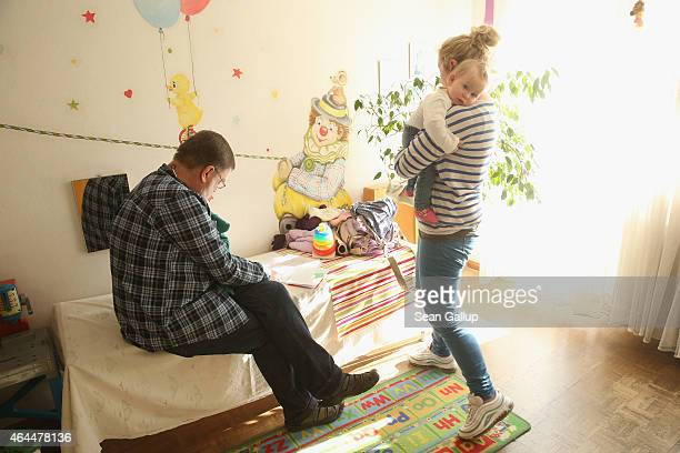 Children's doctor Juergen Hochfeld chats with a mother and her 11monthold daughter Tijana prior to injecting Tijana with a vaccine against measles...