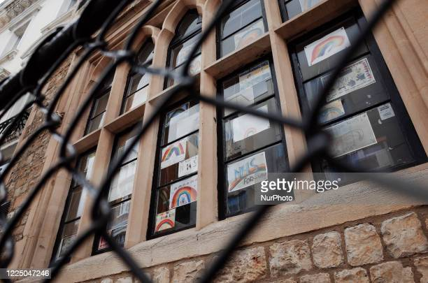 Children's drawings of rainbows and messages of support for the National Health Service cover the windows of a primary school in the Lancaster Gate...