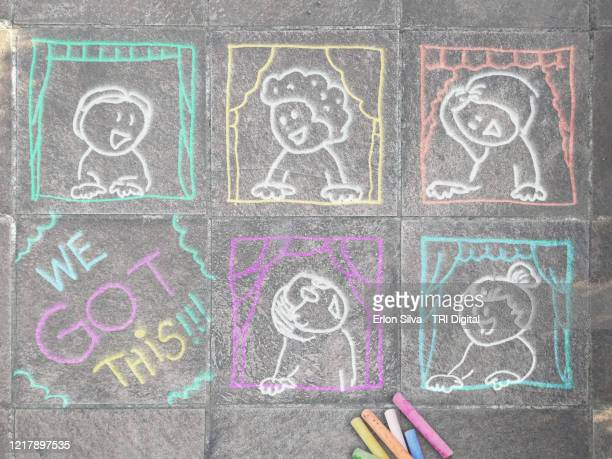 childrens drawings on the floor passing the concept of building neighbors in social distance with the message of we got this along a quarantine - chalk art equipment stock pictures, royalty-free photos & images