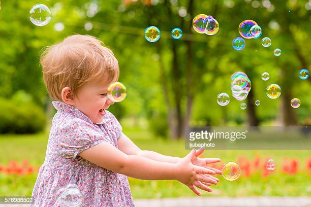 children's entertainment, Child playing with soap bubbles outsid