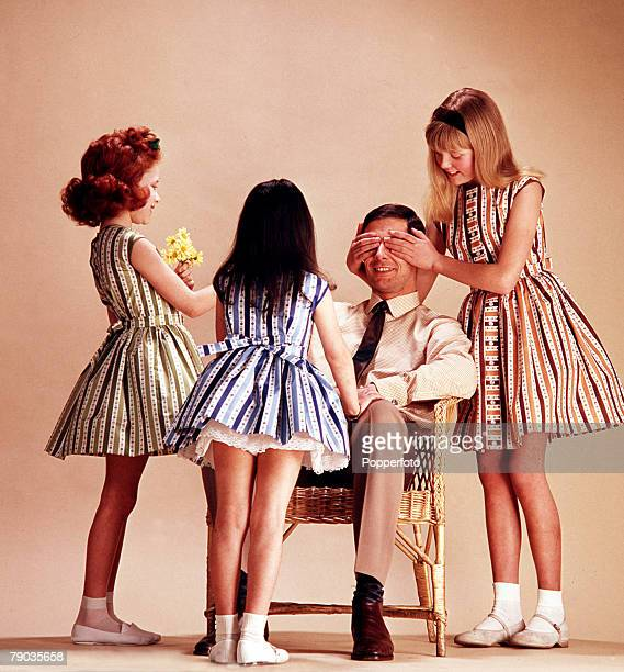 Three young girls wearing striped sleeveless summer dresses with full skirts and petticoats surprise a seated man with a bunch of flowers