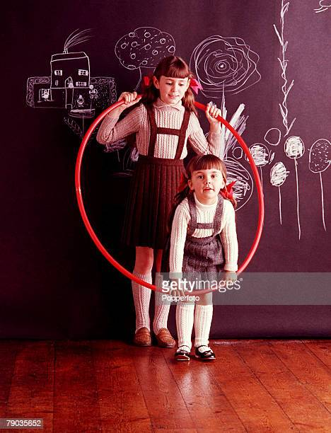 Two young girls wearing pleated woollen skirts over light Aran knit sweaters play with a red hula hoop Behind them there is a wall hanging covered in...