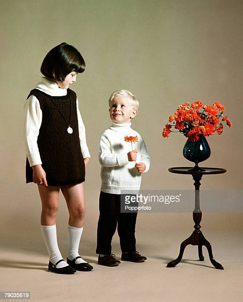 Smiling young boy wearing a white polo neck sweater holds an orange flower that he has removed from a vase as an older girl wearing a white polo neck...