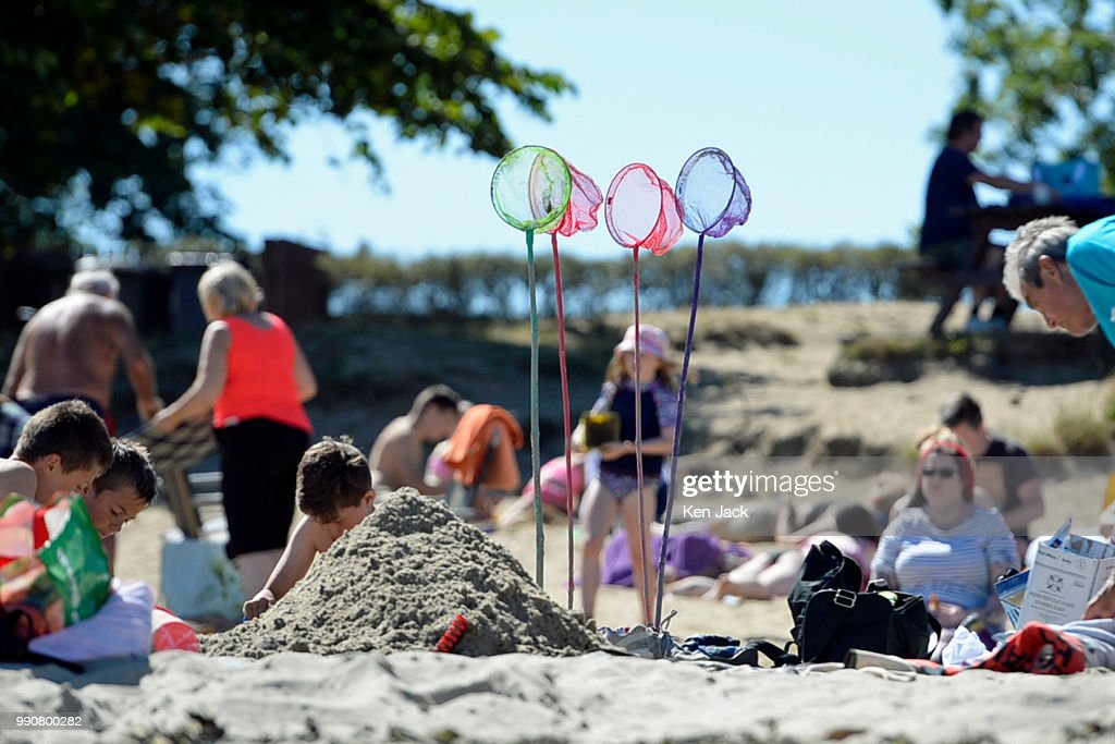 Children's fishing nets stuck into the sand as people enjoy the sun on Silver Sands beach at the start of the Scottish school holidays as the heatwave continues, on July 3, 2018 in Aberdour, Scotland.