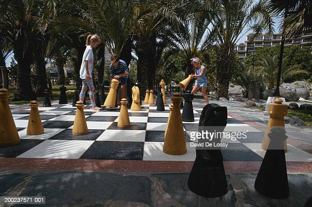 Children's hands on chess board playing with chess piece in garden