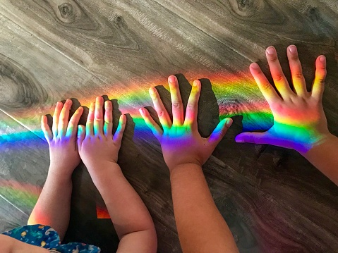 Children's hands playing with a rainbow 1172368088