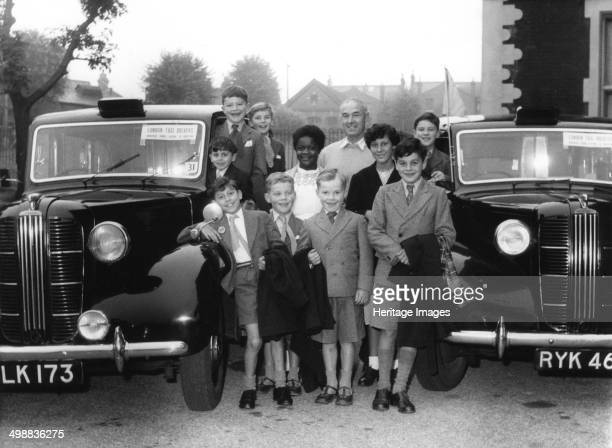 Children's home outing Norwood London A group of children from the Wood Vale London County Council Home pose with taxis