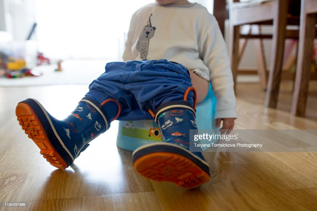 Children's legs in boots, hanging down from a chamber-pot on a home interior : Stock Photo