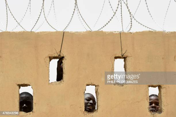 Childrens look through holes of a wall on June 3 2015 at the MINUSMA camp on June 3 2015 in Goundam in the Timbuktu region during the joint operation...