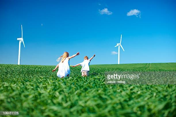 Childrens play in field & wind turbines