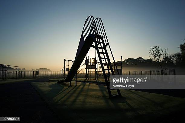 A childrens playground with climbing frames and slides is surrounded by mist at sunrise on June 20 2010 in London England The Conservative government...