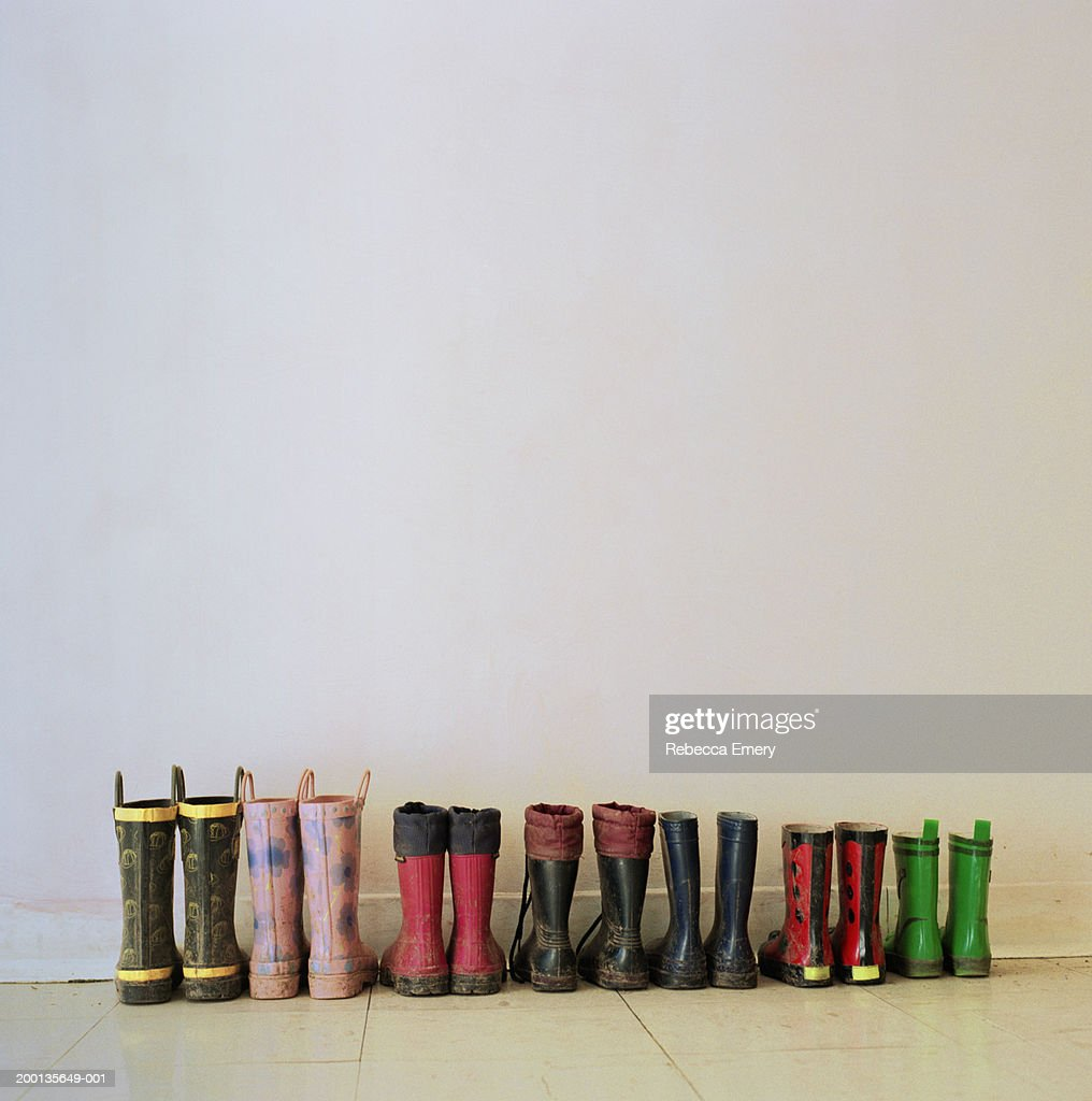 Children's rain boots lined up against the wall : Stock Photo