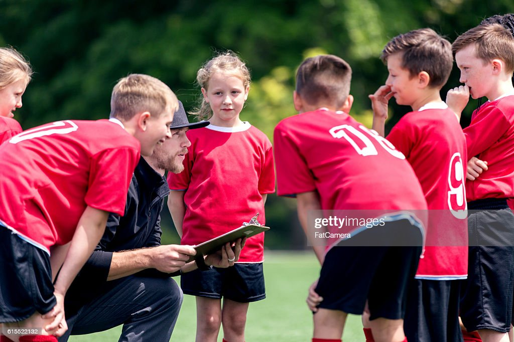 Childrens soccer coach talking to his co-ed team : Stock Photo
