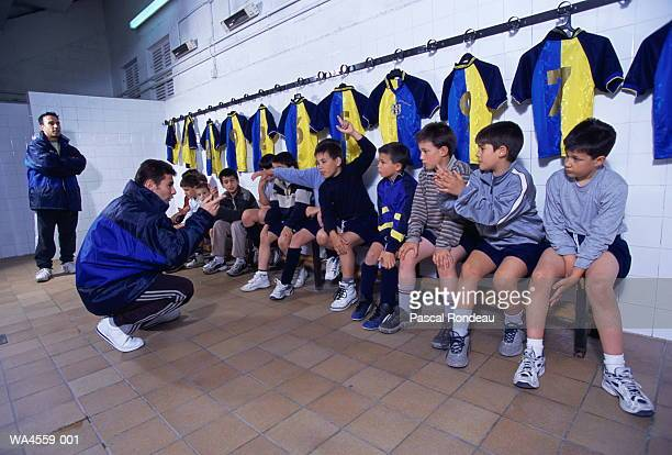 Children's soccer coach talking to players in locker room
