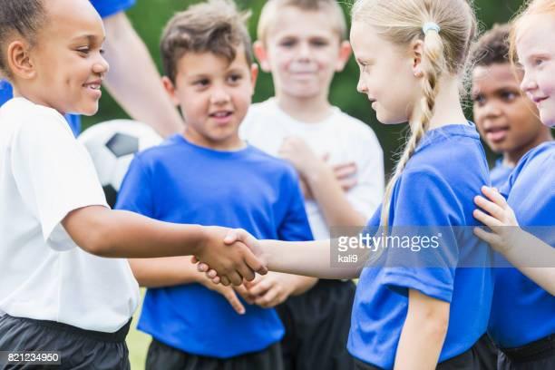 Children's soccer team, girls shaking hands