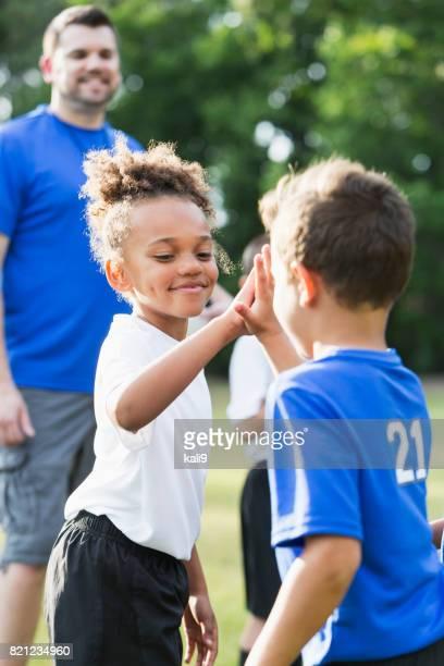 Children's soccer team, opponents giving high-fives