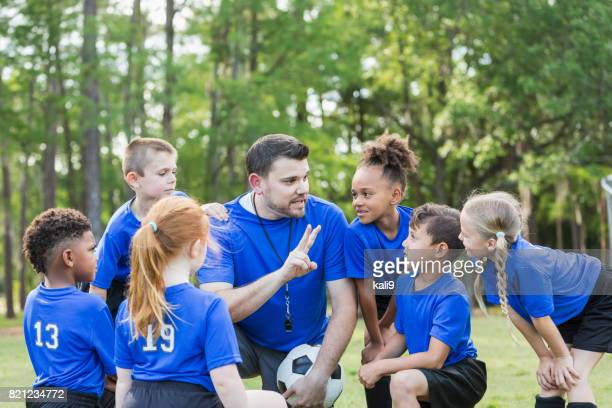 children's soccer team with coach - coach stock pictures, royalty-free photos & images
