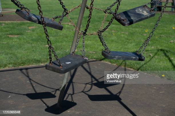 Childrens swings chained and padlocked together to prevent their use in a communal playground and fitness area which has been closed by order from...