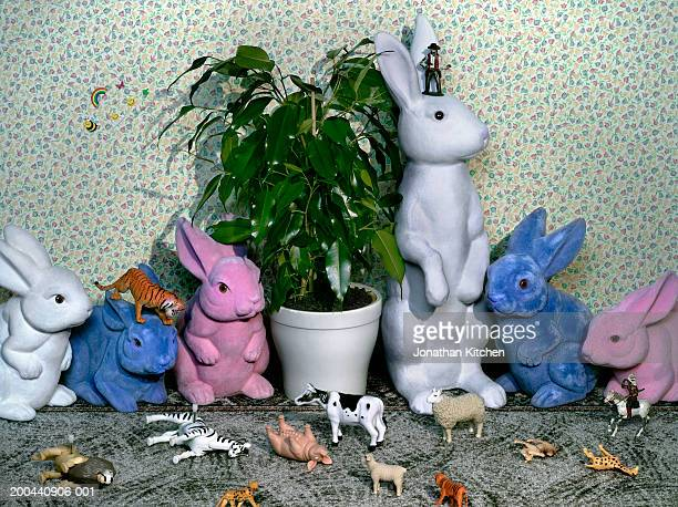 Children's toy animals gathered around potted plant, close-up