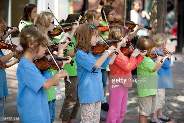 children's violin ensemble at a street performance - violin family stock photos and pictures