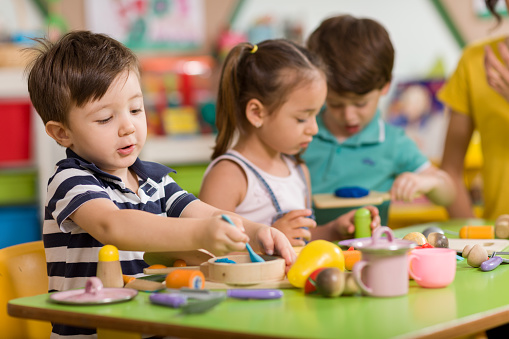 Childs are playing with play clay in classroom. 998670532