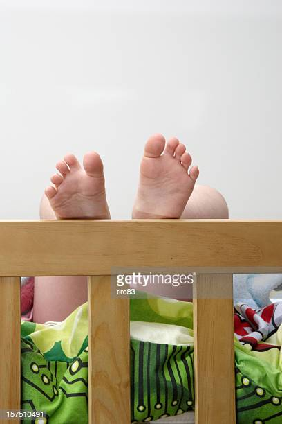 Child's bare feet on bedstead