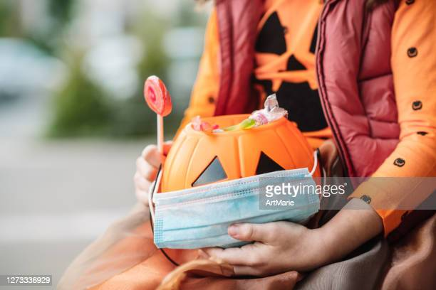 child's basket with sweets and protective face mask on halloween in autumn - halloween stock pictures, royalty-free photos & images