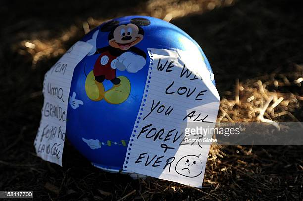 """Child's beach ball with a note in Portuguese saying, """"God has a great party for you guys in heaven,"""" and another one in English, """"We will love you..."""