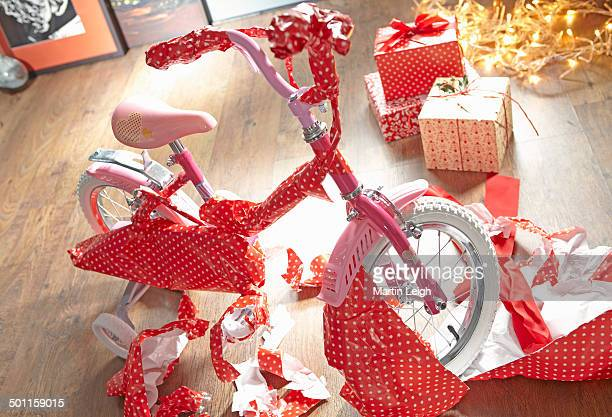 A child's bike as  present partly unwrapped