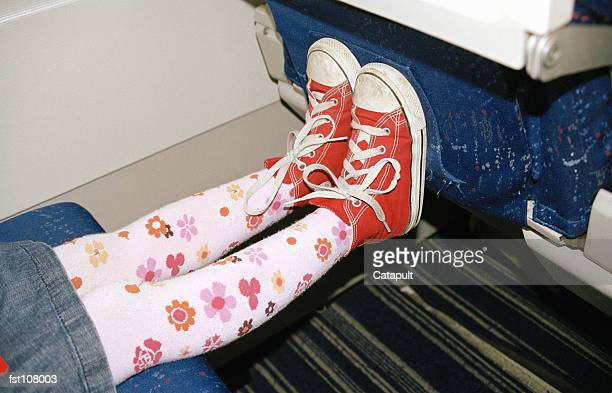 Child?s feet against airplane seat