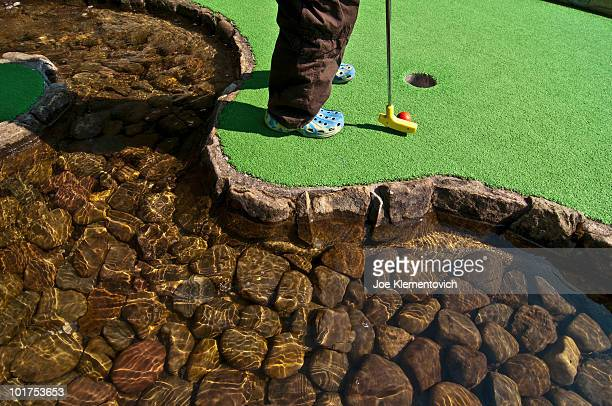 A child's feet at the water hazard while playing mini-golf on a summer day.