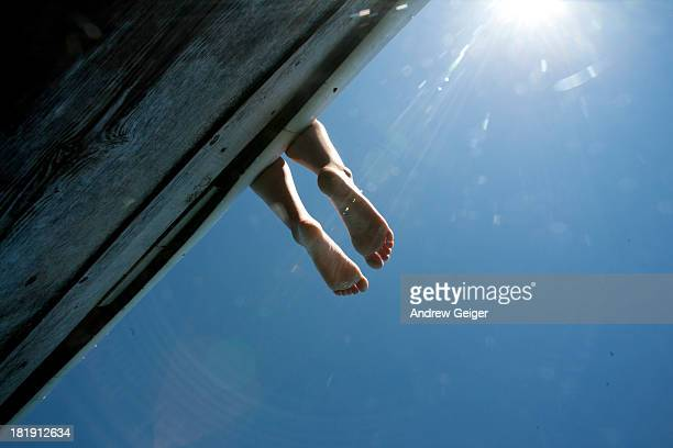 pov of child's feet hanging off dock. - human leg stock pictures, royalty-free photos & images