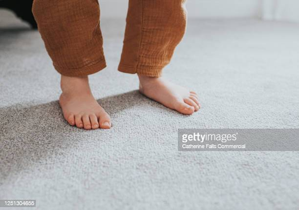 child's feet on grey thick pile carpet, casting shadow - nylon feet stock pictures, royalty-free photos & images