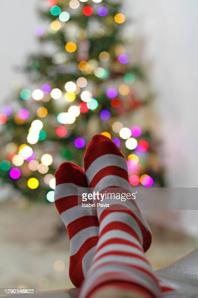 child's feet up with slipper socks in front of christmas tree - low section stock pictures, royalty-free photos & images