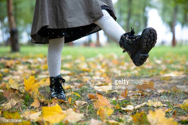 child's feet while walking in the autumn park. - ankle boot stock pictures, royalty-free photos & images