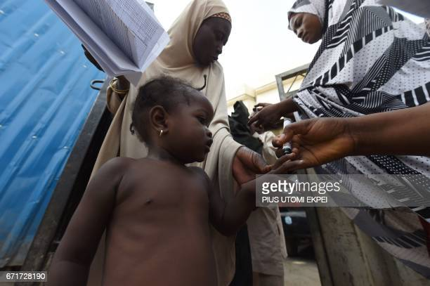A child's finger is being marked as proof to show that she has been immunised during a vaccination campaign against polio at HotoroKudu Nassarawa...