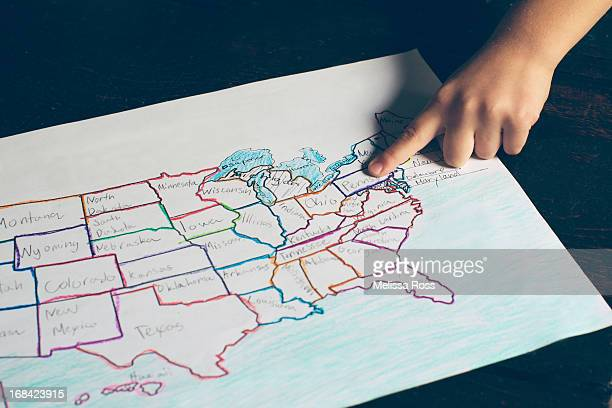 Child's finger pointing to a United States map.