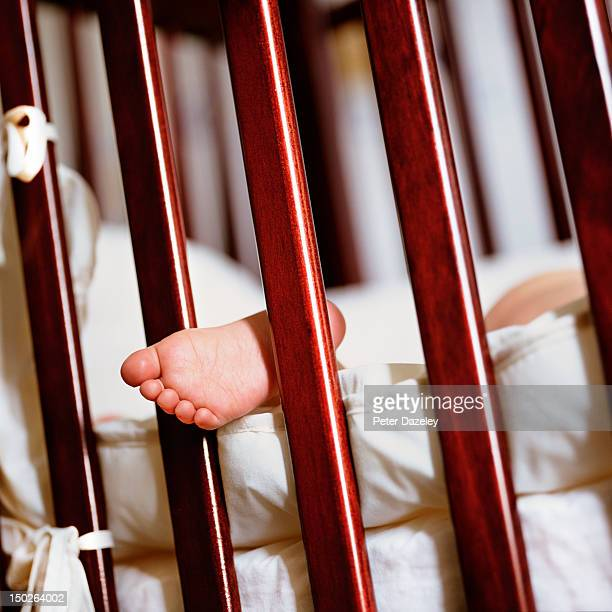 A child's foot sticking through the bars of a cot