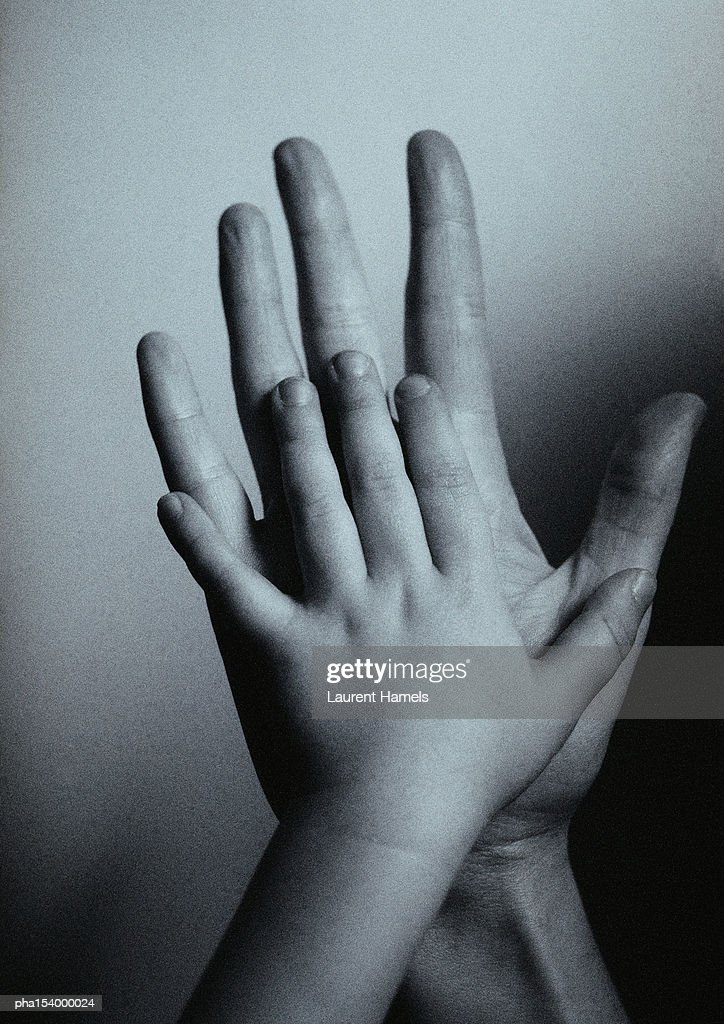 Child's hand against man's hand, palm to palm, close-up, b&w. : Stockfoto