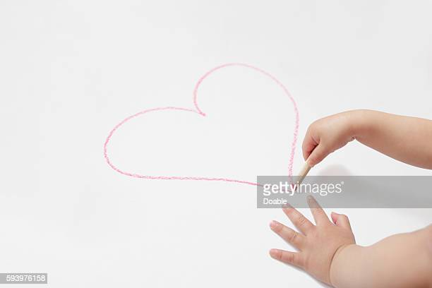 Child's hand drawing heart shape