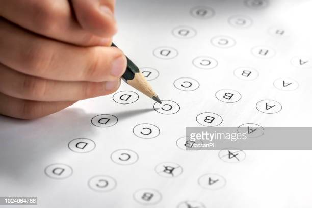 child's hand filling in a multi-answer test with a pencil - survey stock photos and pictures
