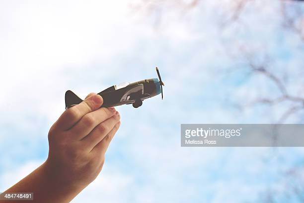 Child's hand flying a toy airplane outside