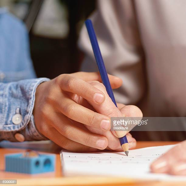 Child's hand guiding adult's hand through writing exercise