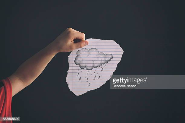 child's hand holding a drawing of a rain cloud
