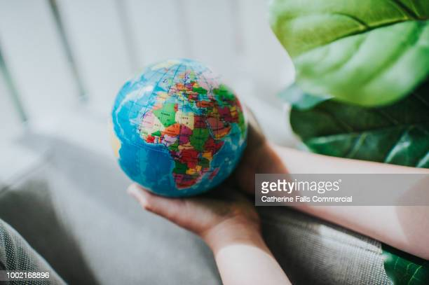 childs hand holding a globe - map of africa stock photos and pictures