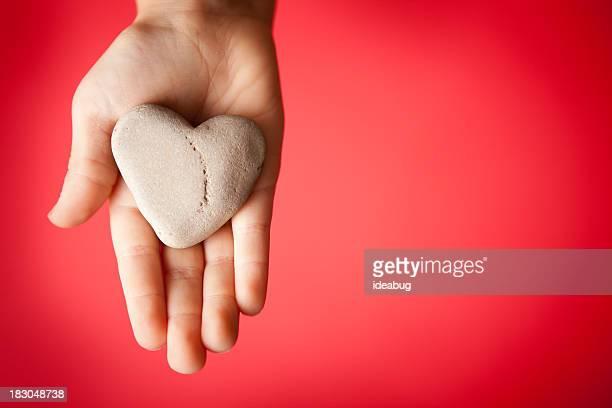 Kind, die Hand hält einen herzförmigen Stein auf rotem Hintergrund