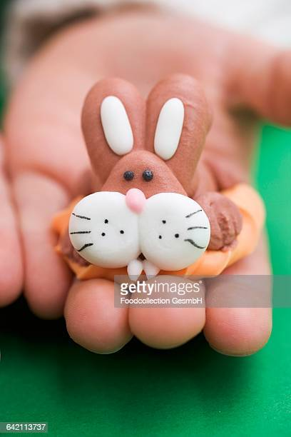 Childs hand holding marzipan Easter Bunny